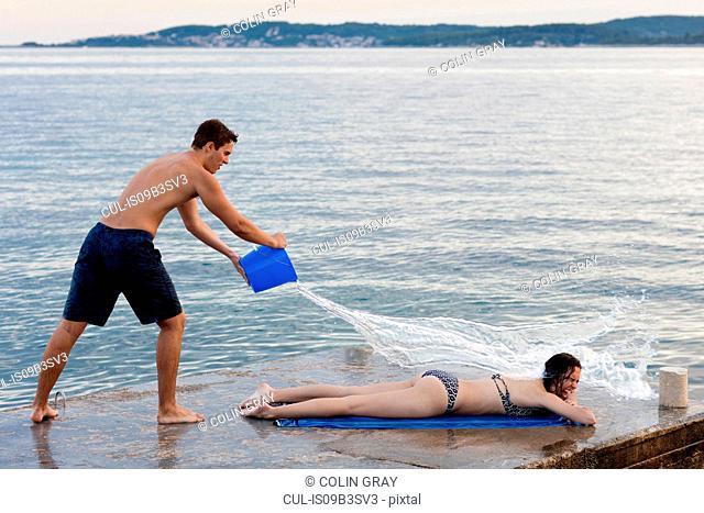 Young man throwing bucket of water over female sunbather, Orebic, Croatia