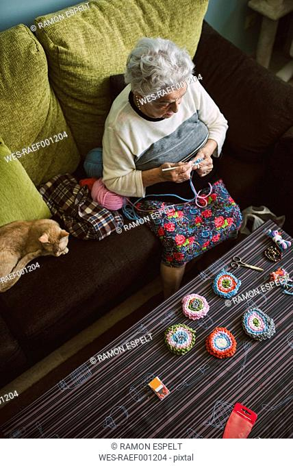 Crocheting senior woman sitting on couch beside her sleeping cat