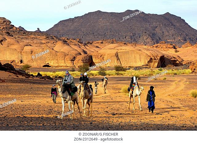 Abenteuerlustige Touristen mit Dromedaren auf einer Exkursion im Akkakus-Gebirge, Sahara, Libyen / Adventurous tourists with dromedaries on an excursion in the...