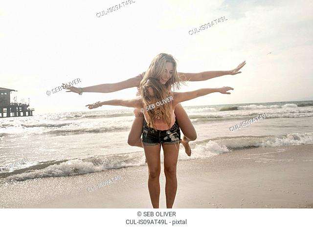 Two young women playing piggy backs with arms open on beach