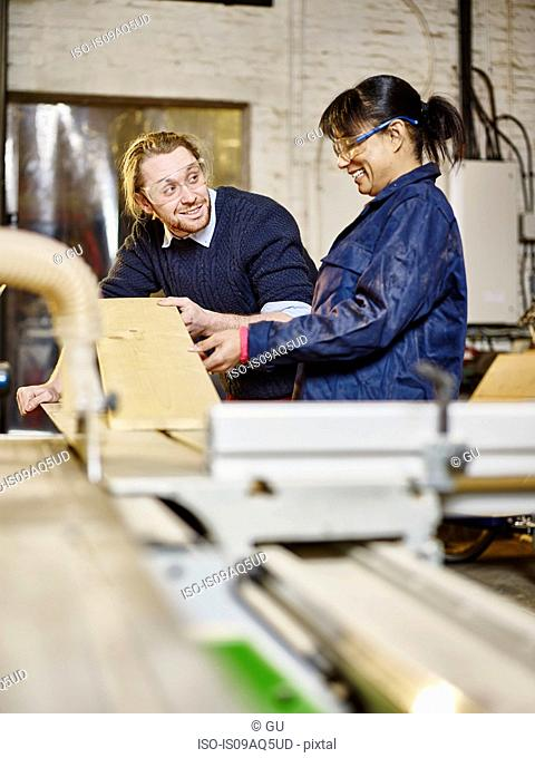 Man and female trainee preparing wood plank in printing workshop