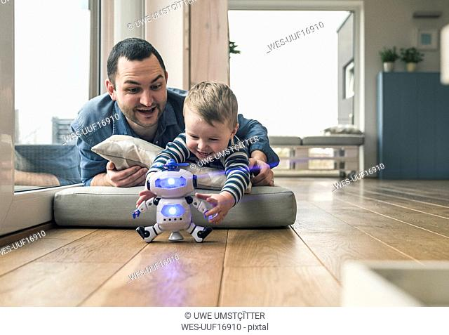 Excited father and son lying on a mattress at home playing with a toy robot