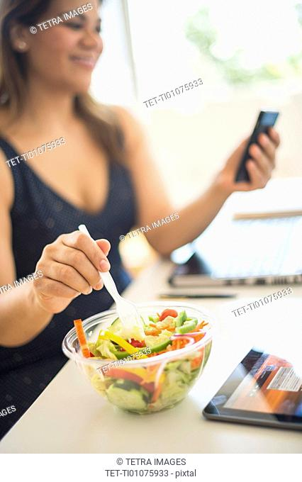 Woman eating salad and using mobile phone in office