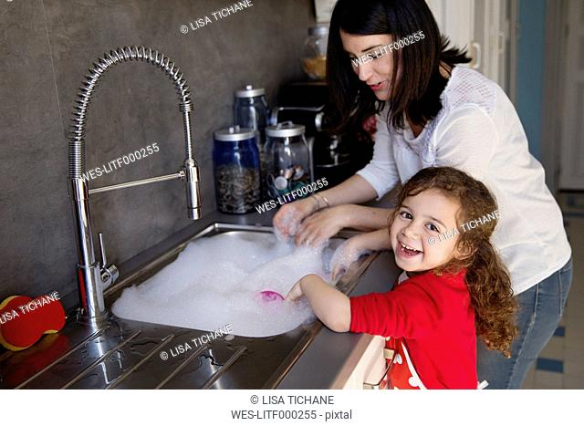 Portrait of little girl washing dishes together with her mother