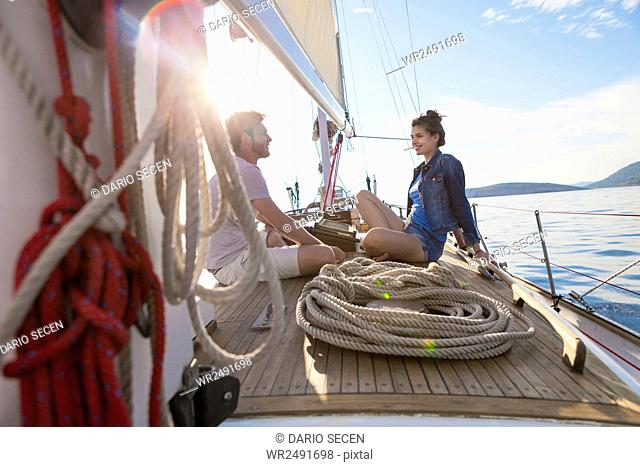 Young couple sitting face to face on sailboat