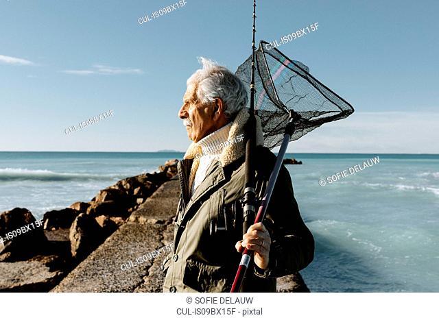 Senior man going fishing, Livorno, Italy