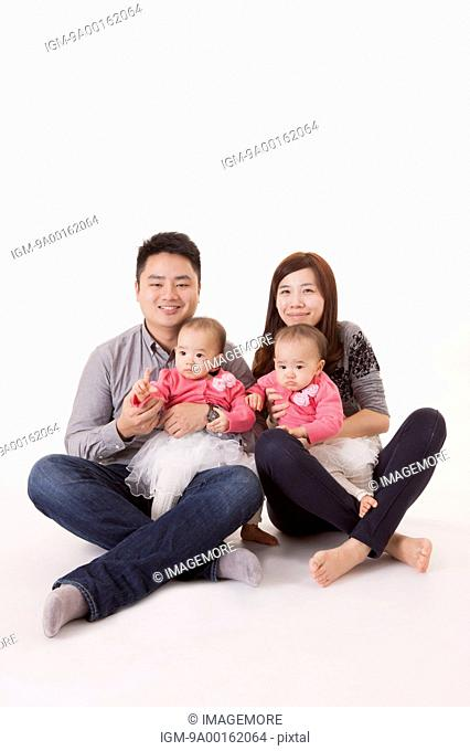 Young family with baby twins smiling