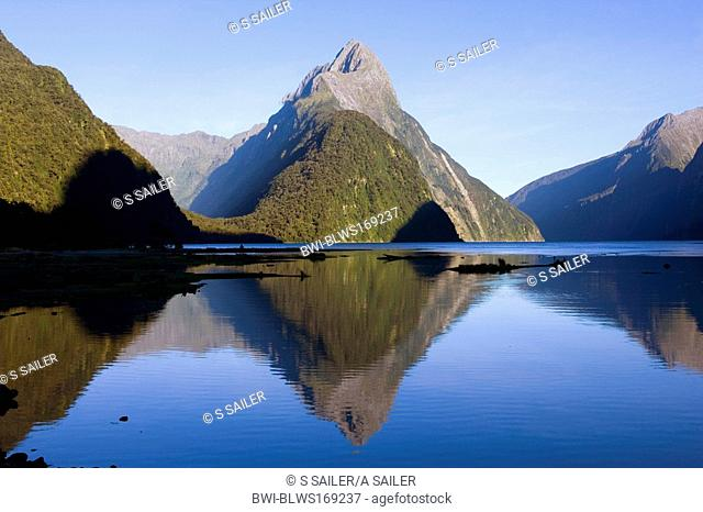 Milford Sound, landmark Mitre Peak and surrounding mountains reflected in the calm waters of Milford Sound in early morning, New Zealand, Southern Island