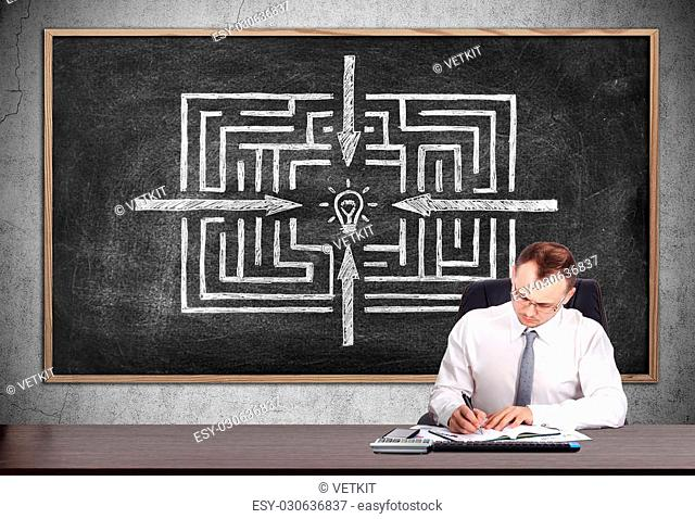 businessman signs a contract and blackboard with drawing labyrinth