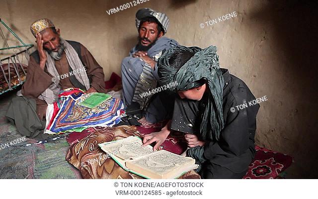 Afghan boy putting on a turban, kabul