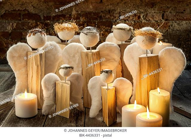 Christmas decoration, group of handcrafted angels on old wooden table, lit white candles, in front of brick wall