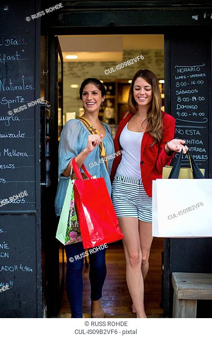 Two young female friends leaving cafe carrying shopping bags