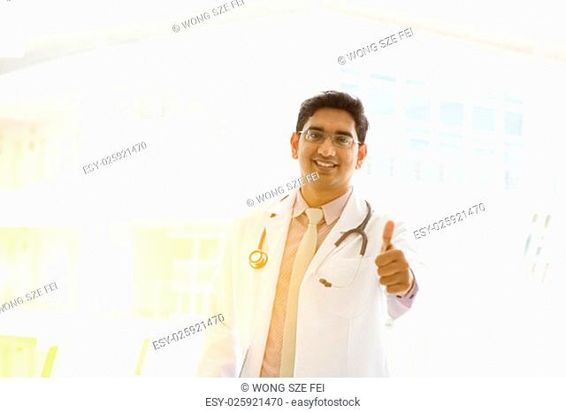 Portrait of a smiling Asian Indian male medical doctor in uniform thumb up, standing outside hospital building block, beautiful golden sunlight at background