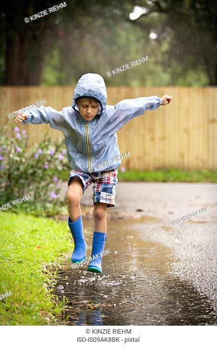 Boy in rubber boots jumping in rain puddle