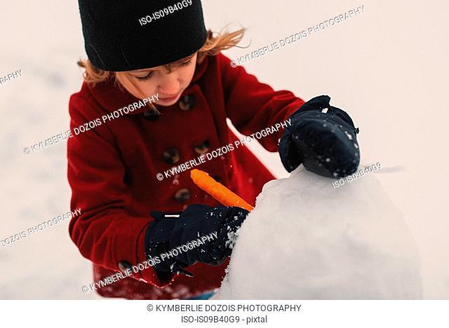 Girl using carrot for snowman's nose