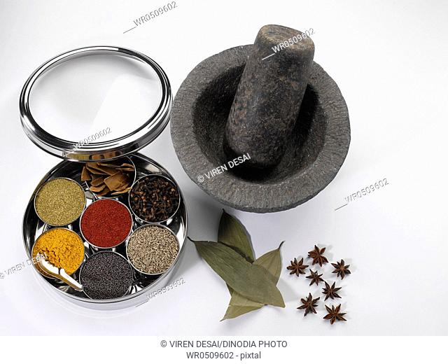 Different types of spices in bowls in stainless steel box with old stone grinder