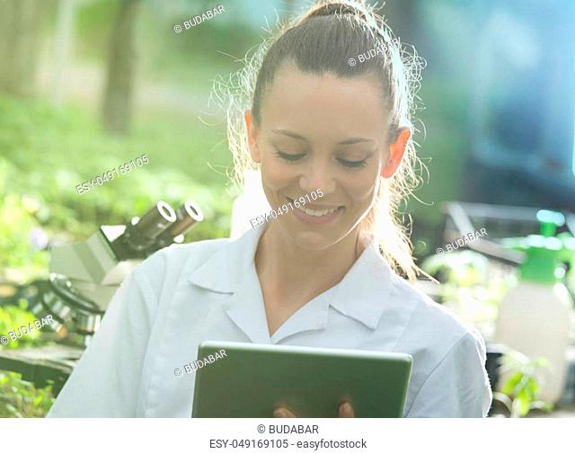 Young pretty woman agronomist in white coat working on tablet and microscope in greenhouse. Plant care and protection concept