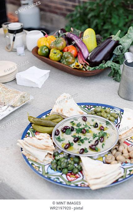 Large bowl of vegetables, dips and bread on a table in a garden