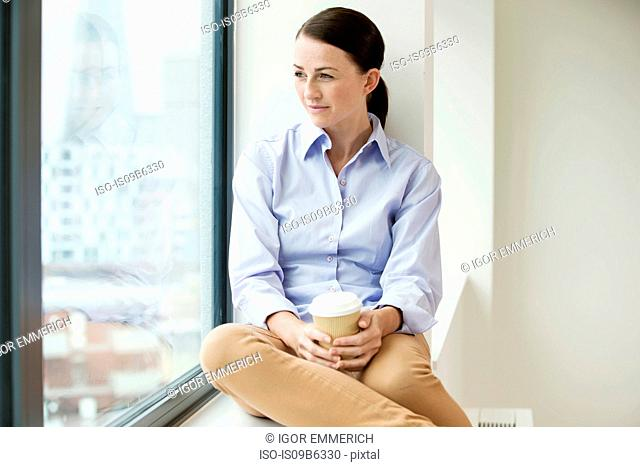 Businesswoman sitting on window ledge, looking out of window, holding takeaway coffee up