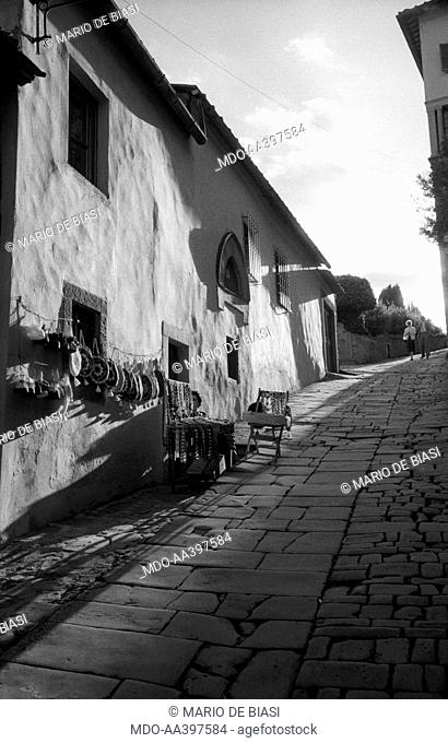 Two people walking in a paved street. On the left, a woman with her bags stall. Fiesole, 1950s