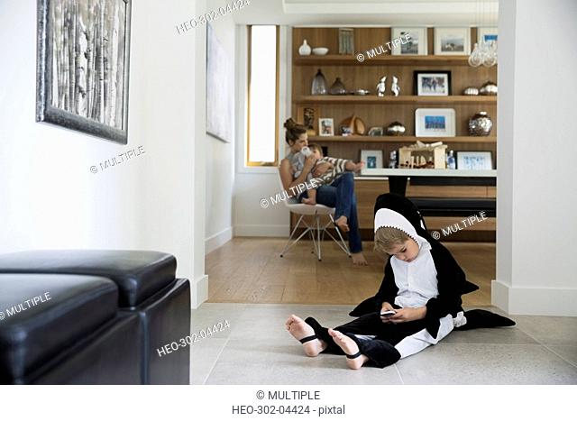 Boy in killer whale costume using cell phone on floor