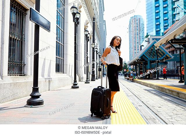 Businesswoman waiting on light rail platform