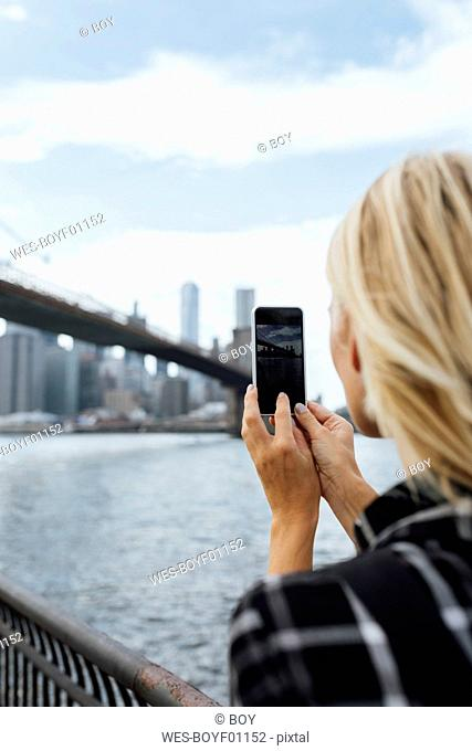 USA, New York City, Brooklyn, young woman at the waterfront taking a cell phone picture of Brooklyn Bridge
