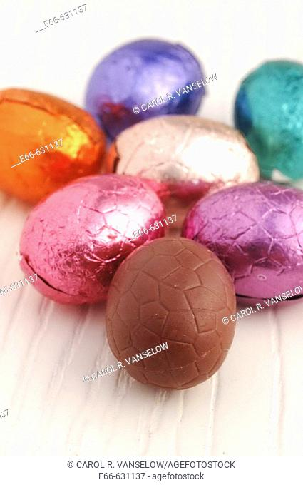 Foil-wrapped chocolate Easter eggs on whitewashed wood background