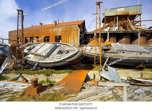 Old boats in abandoned whaling station full of broken machinery, collapsing buildings, barrels, pipes and tanks, Leigh Harbour