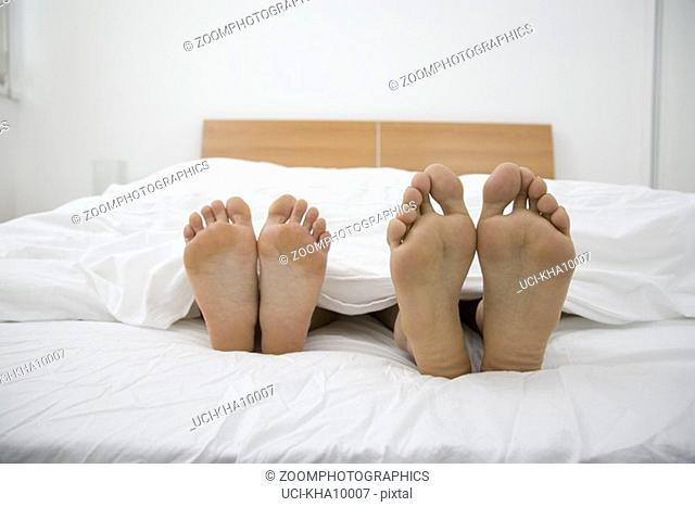 Close up of barefeet, couple sleeping in bed