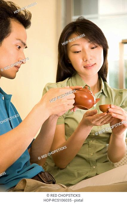 Young man pouring tea into a cup held by a young woman
