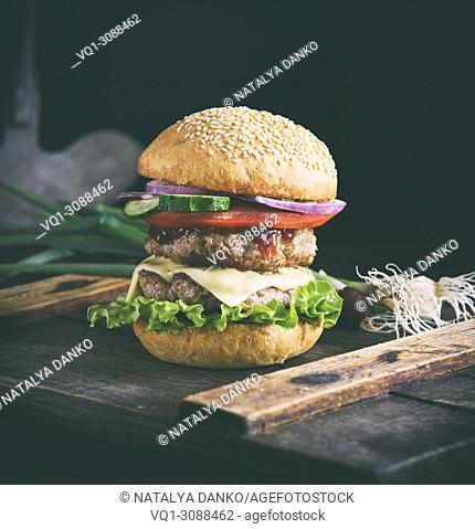 sandwich with two meat cutlets, cheese and vegetables, a cheeseburger on a brown wooden board, vintage toning