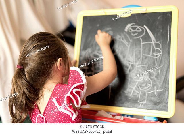 Little girl drawing on chalk board in children's room