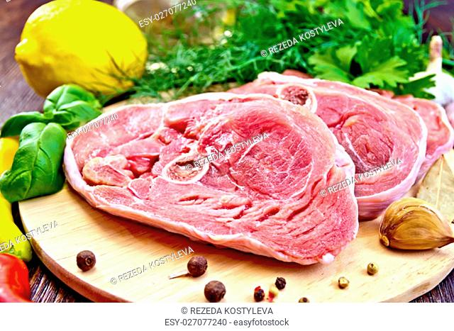 Steak meat raw turkey with pepper, basil, lemon and garlic, vegetable oil on the background of wooden boards