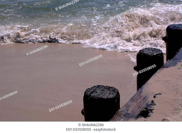 A wave washes up alongside a jetty