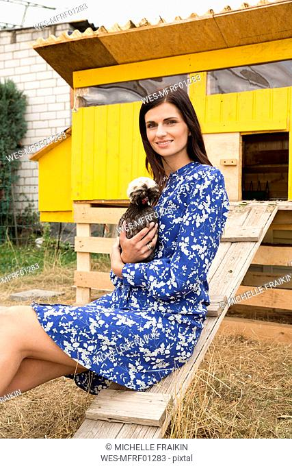 Portrait of smiling woman with Polish chicken at chickenhouse in garden