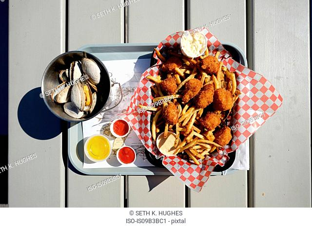 Overhead view of fried seafood and french fries on tray with bowl of scallops, Lunenburg, Nova Scotia, Canada