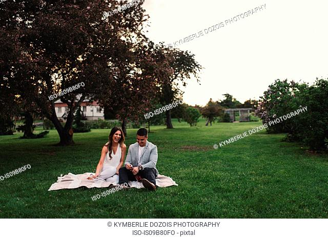 Romantic young couple opening pink champagne in park at dusk