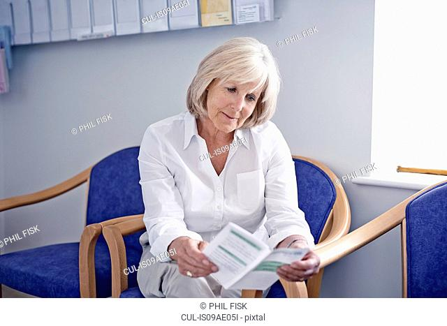 Mature female patient reading leaflet in hospital waiting room