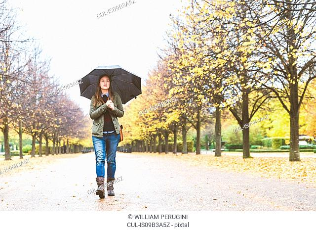 Young woman walking through park, carrying umbrella