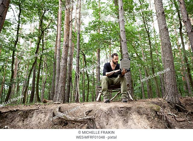 Man sitting on self-made wooden chair in forest using laptop