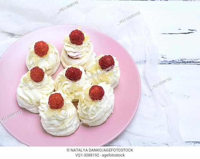 baked cakes made of egg white and whipped white cream with raspberries on a pink plate, Pavlova dessert