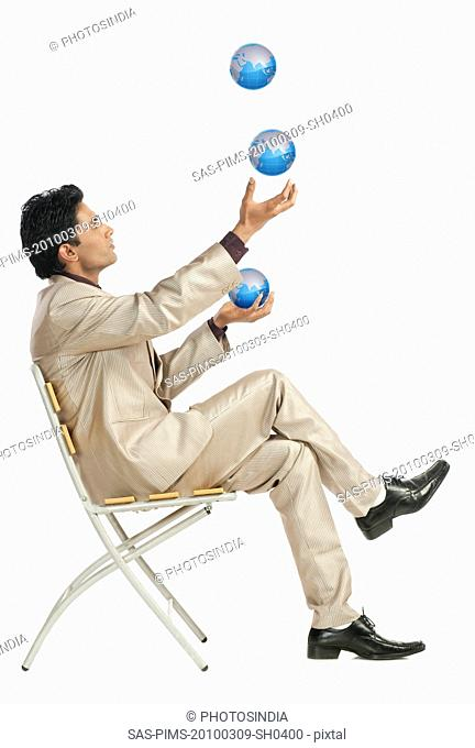 Businessman sitting on a chair and juggling with globes