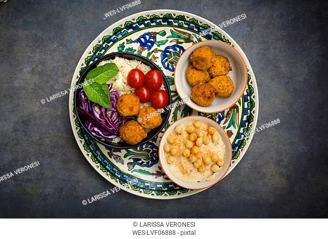 Couscous sweet potato falafel bowl with red cabbage, tomato, mint and hummus