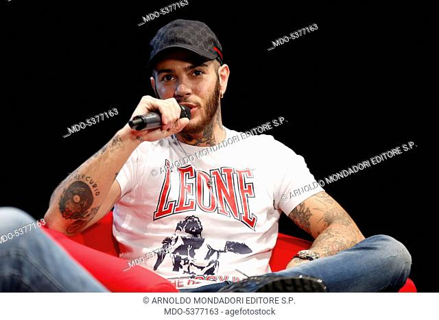 The rapper Emis Killa (Emiliano Rudolf Giambelli) being interviewed by the journalist Gianni Poglio at the meeting Panorama d'Italia. Milan, Italy