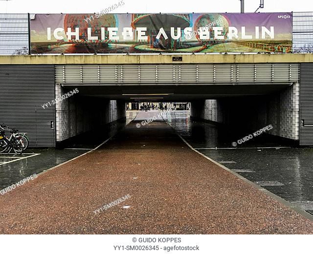 Tilburg, Netherlands. Banner: 'Ich Liebe aus Berlin' above a railroad and bicycle intersecting tunnel, bordering the city's RailRoad Zone and the city's RAW...