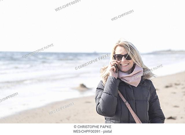 Portrait of happy woman on the phone on the beach