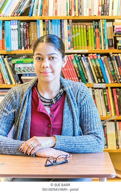 Portrait of mature female student in front of bookshelf