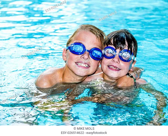 two funny boys wearing swimming goggles, embracing each other