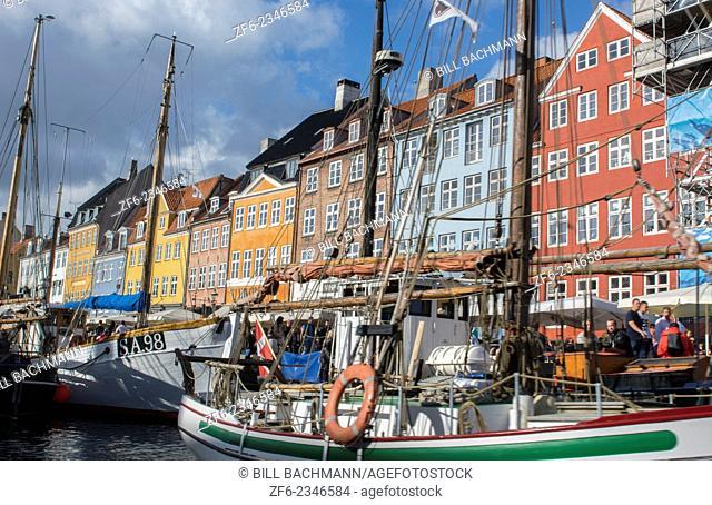 Copenhagen Denmark famous Nyhavn color homes and boats with crowds Kobenhavn tourists